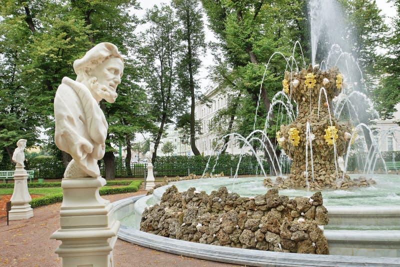 Le statue e la fontana antiche nei giardini dell'estate parcheggiano fotografia stock libera da diritti