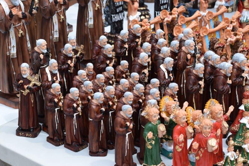 Le statue miniatura del padre Pio del san sono visualizzate per la vendita sull'iarda della chiesa fotografia stock libera da diritti