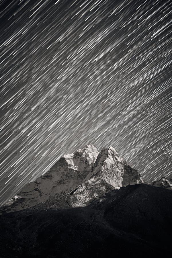 Le stelle che cadono sopra picco di montagna di Ama Dablam si sono accese da una luce della luna luminosa Tracce delle stelle sop fotografie stock libere da diritti