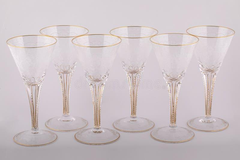 Le Stemware a facetté des verres faits de verre tchèque avec les lignes d'or et les modèles d'isolement sur un fond blanc images stock