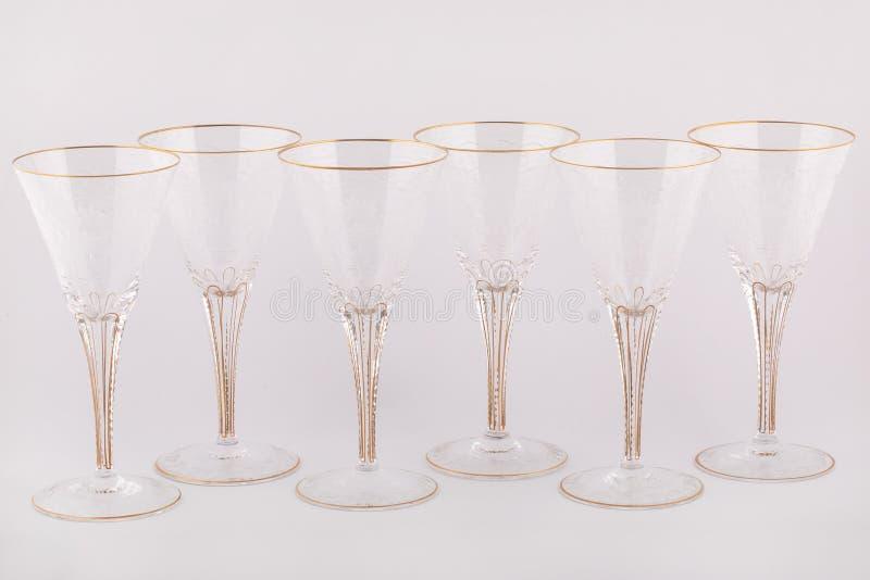 Le Stemware a facetté des verres faits de verre tchèque avec les lignes d'or et les modèles d'isolement sur un fond blanc photographie stock libre de droits