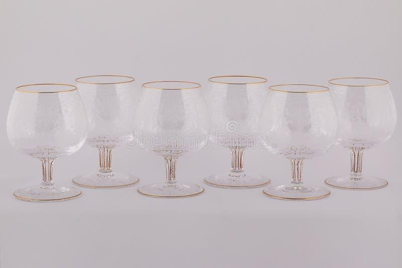 Le Stemware a facetté des verres faits de verre tchèque avec les lignes d'or et les modèles d'isolement sur un fond blanc photographie stock