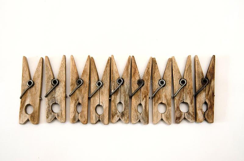 Le stesse vecchie mollette da bucato di legno si trovano in una fila fotografia stock