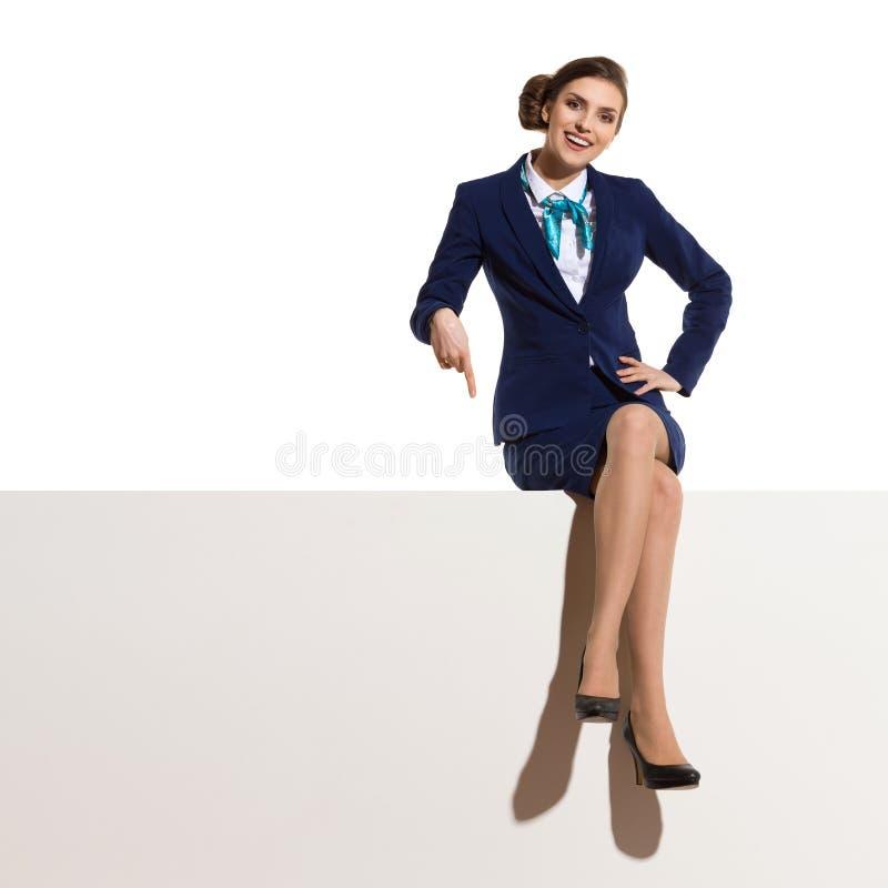 Le stewardessen Is Sitting On ett baner och peka ner royaltyfria bilder