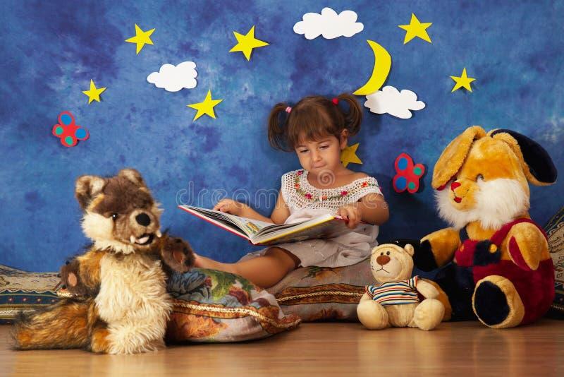 Le storie della lettura della bambina a lei hanno farcito gli amici del giocattolo immagine stock libera da diritti
