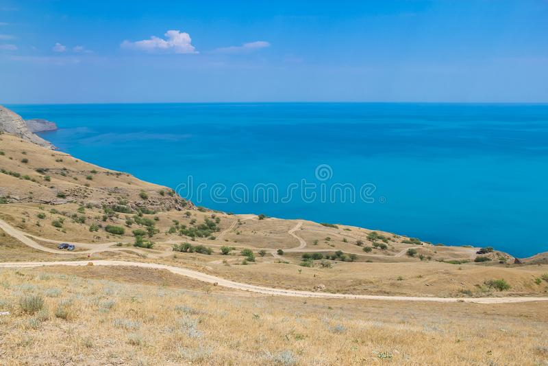 Le strade ed il mare abbelliscono a capo Meganom, la costa Est della penisola della Crimea Fondo variopinto, concetto di viaggio fotografia stock