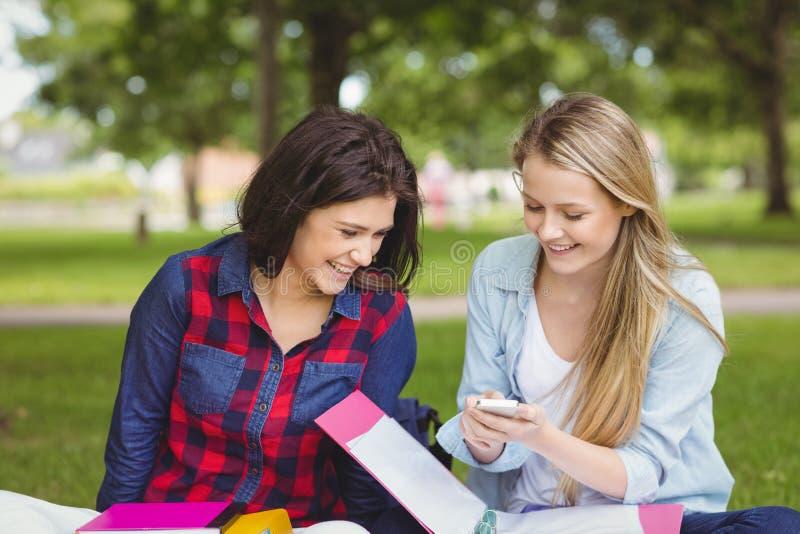 Le studenter som använder smartphonen arkivbilder