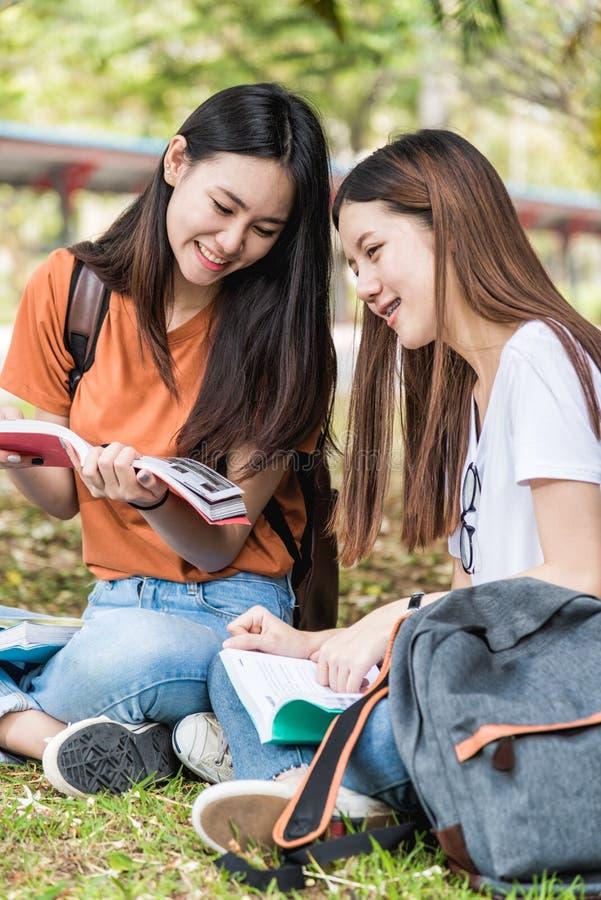 Le studentesse e l'amica sono durante i libri di lettura di seduta o fotografia stock libera da diritti