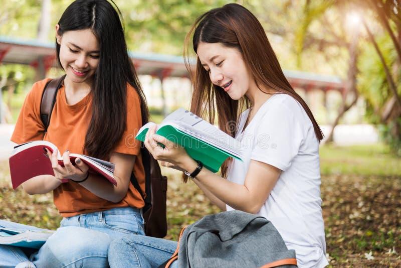 Le studentesse e l'amica sono durante i libri di lettura di seduta o fotografie stock libere da diritti