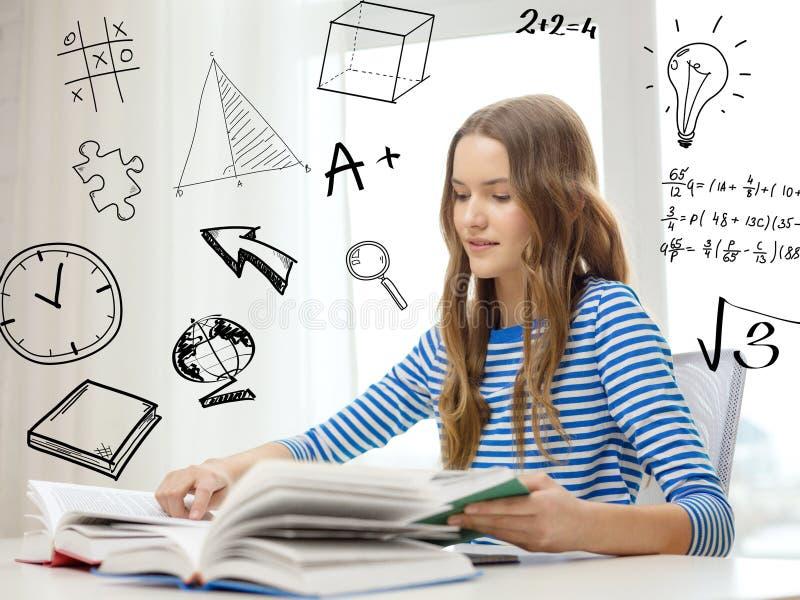 Le studentflickaläseböcker hemma royaltyfri foto