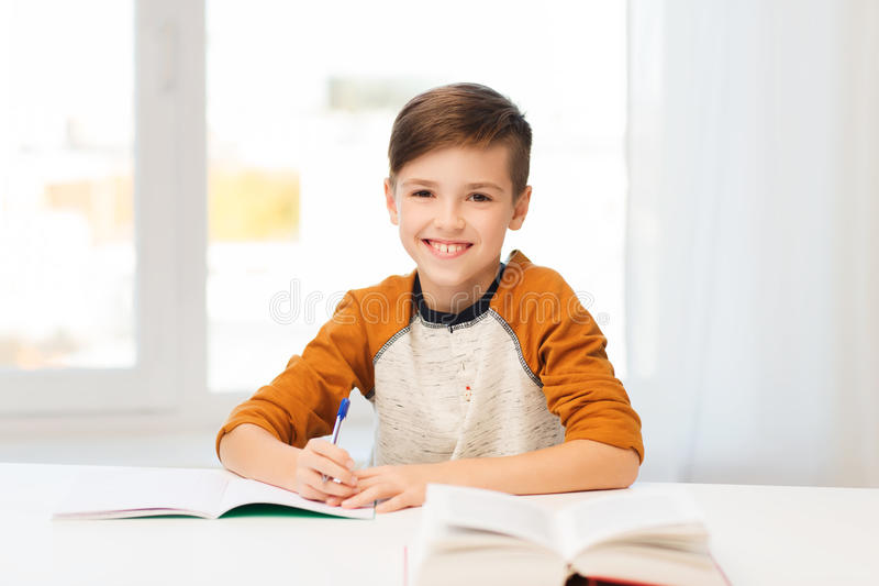 Le studentpojken som hemma skriver till anteckningsboken fotografering för bildbyråer