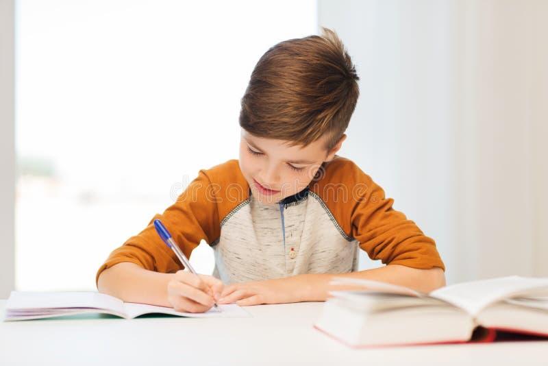 Le studentpojken som hemma skriver till anteckningsboken royaltyfria bilder