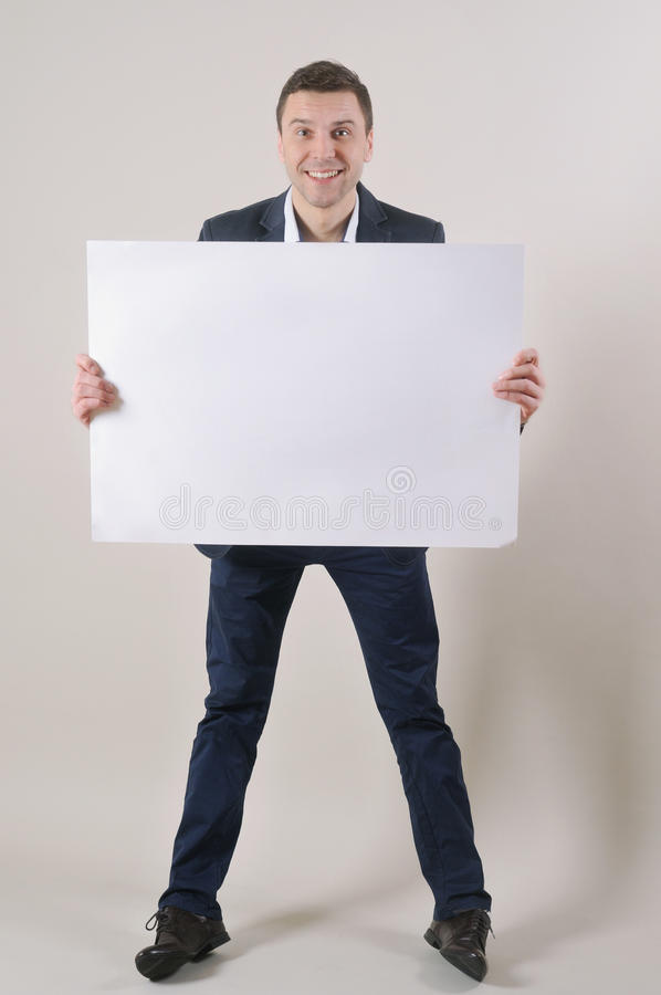 Le studio a tiré d'un homme bel dans un costume supportant une page blanche photo stock