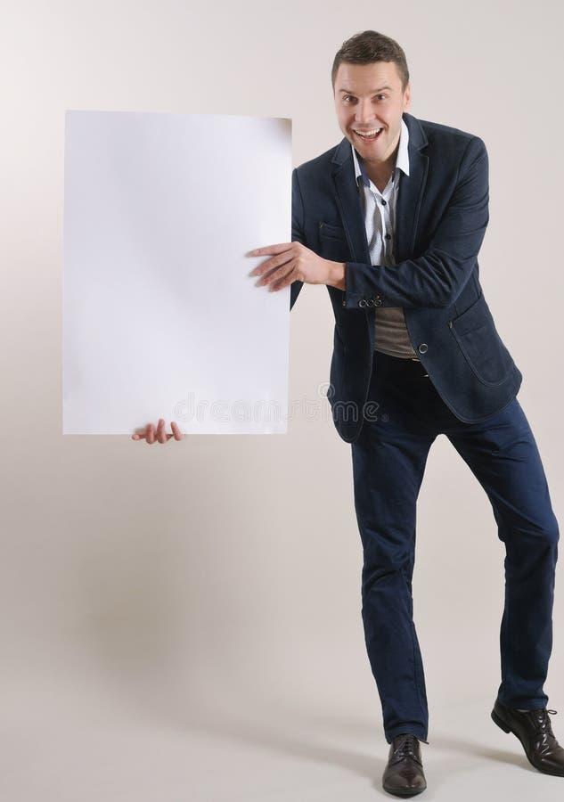 Le studio a tiré d'un homme passionnant dans un costume supportant une page blanche image libre de droits