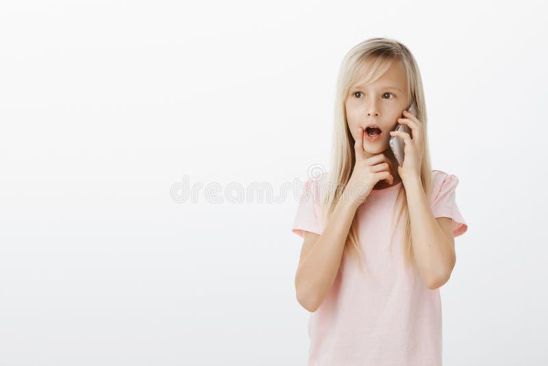 Le studio a tiré de la fille blonde futée curieuse dans le T-shirt rose, parlant sur le smarpthone et tenant le doigt sur la lèvr image stock
