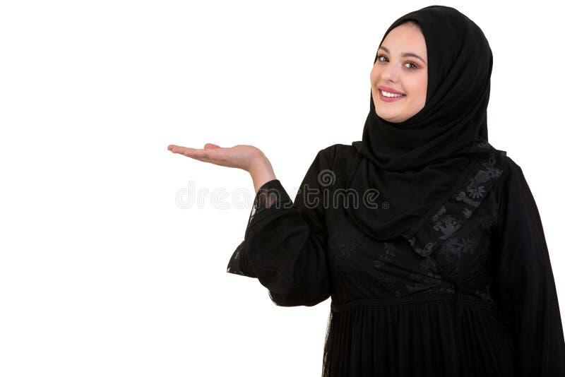 Le studio a tiré de la jeune femme portant l'habillement arabe traditionnel elle ` s tenant sa main sur le côté photo libre de droits
