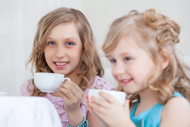Le studio a tiré de petites filles heureuses buvant du thé image stock