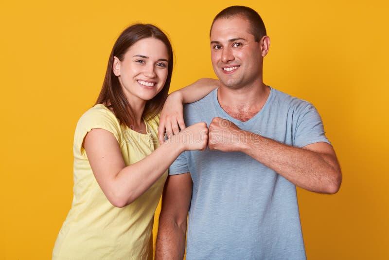 Le studio tiré des couples de sourire heureux de jeune femme et d'homme donnent la bosse de poing regardant la caméra avec l'expr images stock