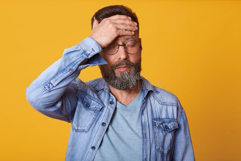 Le studio tiré du jeune homme barbu tendu touche son front et verres mal de tête de avoir, denim habillé, T-shirt gris et, suppor image stock