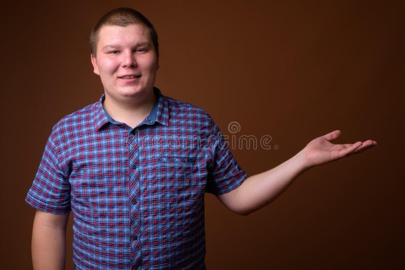 Le studio a tiré du jeune homme de poids excessif sur le fond brun photographie stock libre de droits