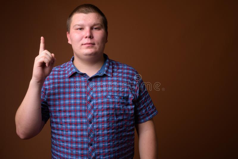 Le studio a tiré du jeune homme de poids excessif sur le fond brun image stock