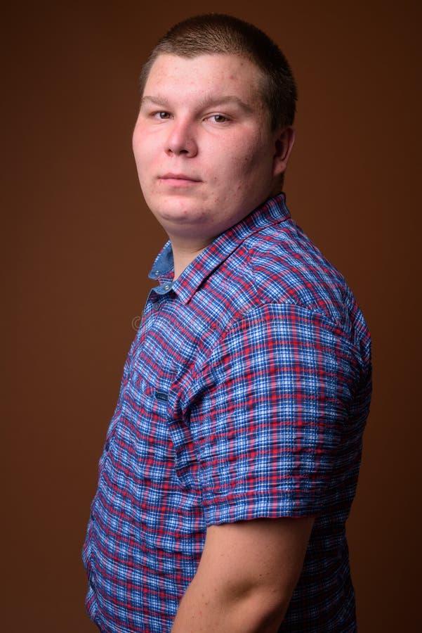 Le studio a tiré du jeune homme de poids excessif sur le fond brun image libre de droits