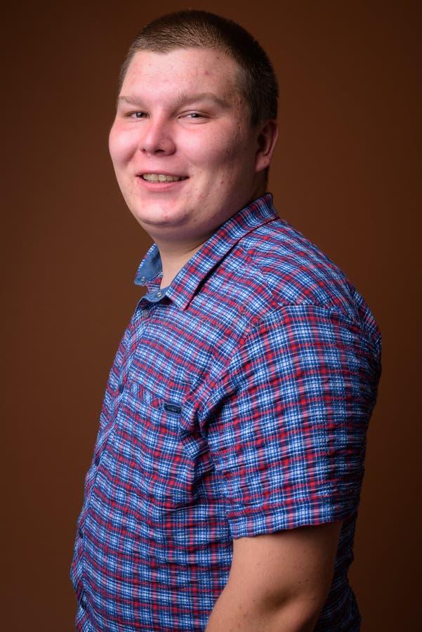 Le studio a tiré du jeune homme de poids excessif sur le fond brun photo stock