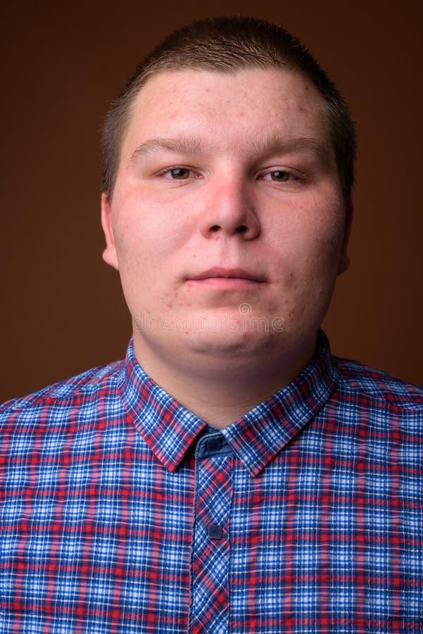 Le studio a tiré du jeune homme de poids excessif sur le fond brun photos libres de droits