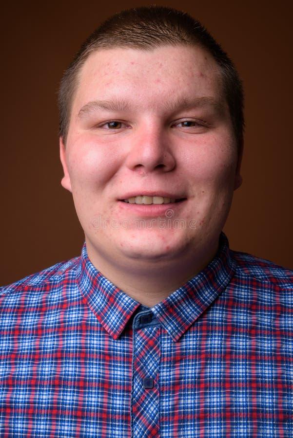 Le studio a tiré du jeune homme de poids excessif sur le fond brun photos stock