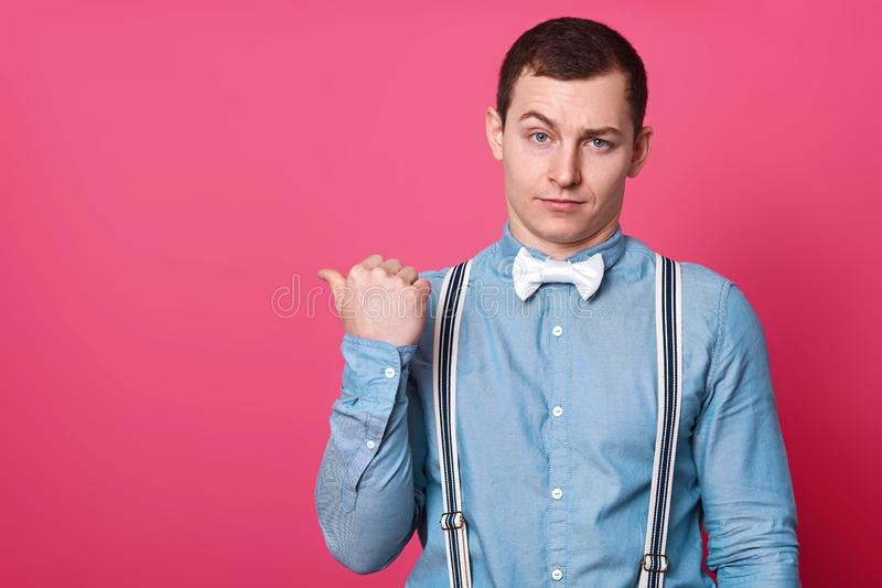 Le studio tiré du mâle attirant dans la chemise bleue, bretelles et noeud papillon blanc, montre avec le doigt de pouce de côté,  photos stock