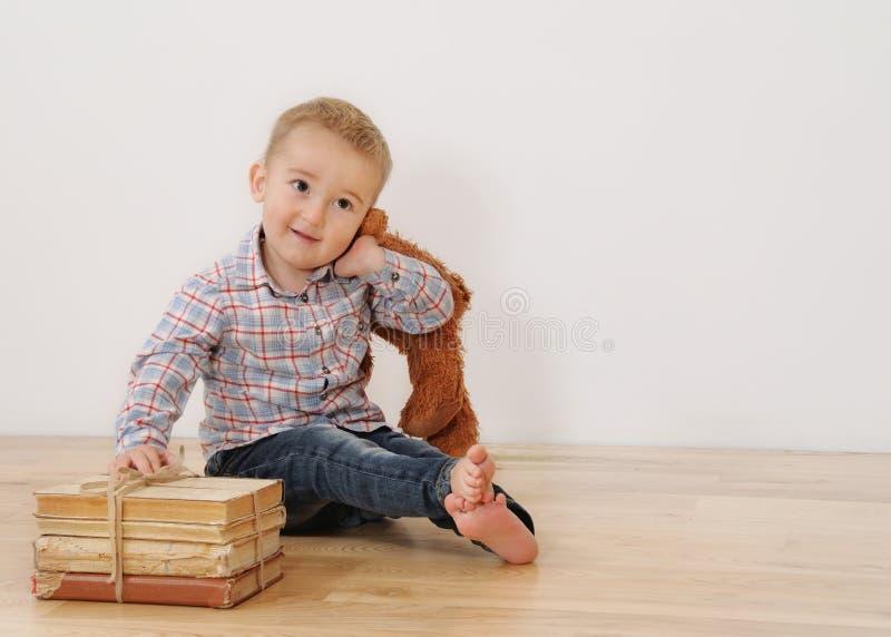 Le studio a tiré du petit garçon de sourire avec son jouet et livres photographie stock libre de droits