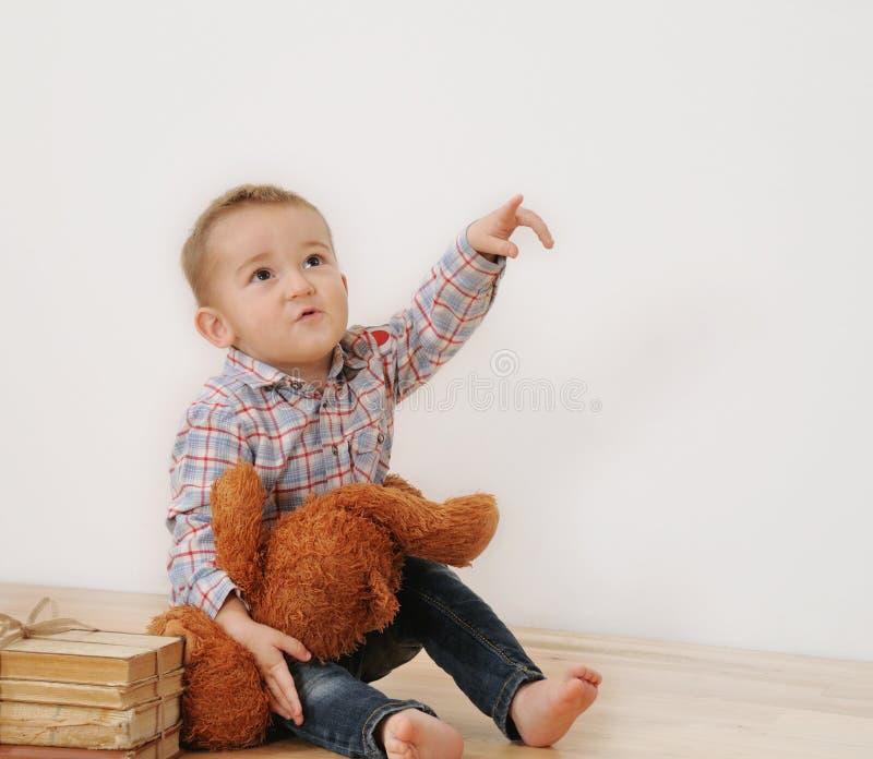 Le studio a tiré du point de petit garçon son doigt avec son jouet et livre photos stock