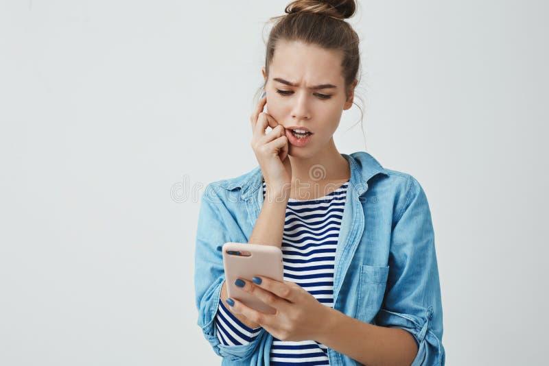 Le studio a tiré la jeune femme 25s mignonne préoccupée perplexe vérifiant la liste de factures en ligne, regard acéré préoccupé  photos stock