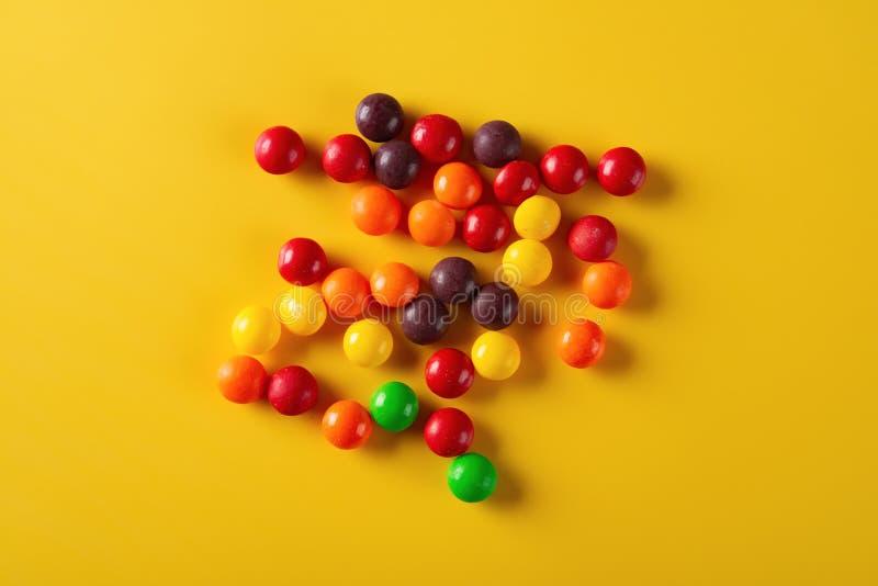 Le studio a tiré les boutons colorés de chocolat de vue supérieure sur le jaune image stock