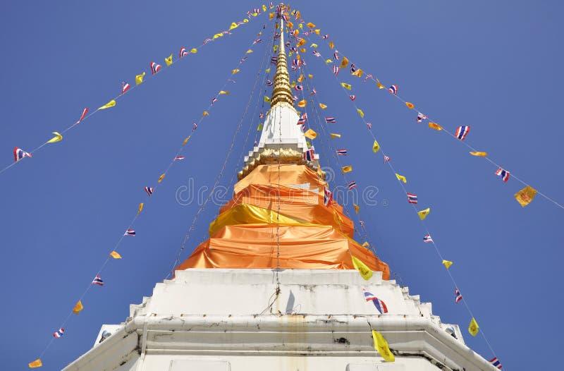 Le stupa en pierre drapé dans le tissu orange monte dans le ciel bleu photographie stock