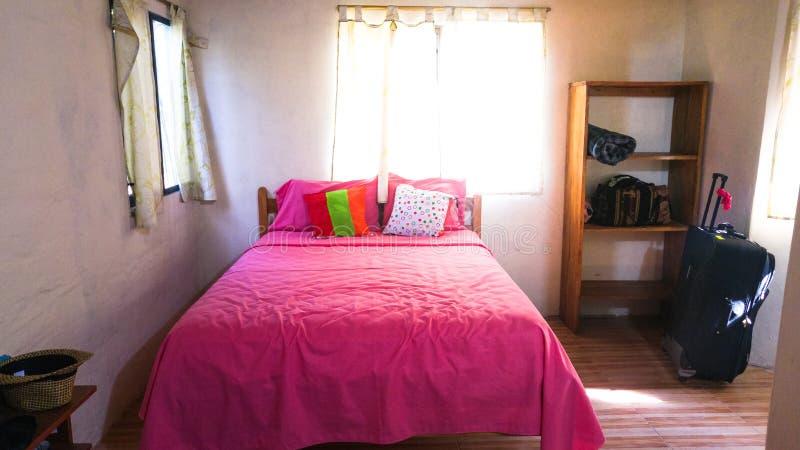 Le style rustique d'une salle aux nuances de blanc et de rose avec un lit en bois photo stock
