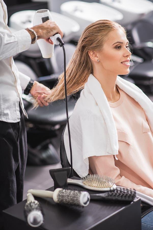 Le styliste en coiffure est les cheveux de séchage photo stock