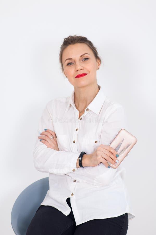 Le styliste féminin avec les cheveux blonds s'assied sur la chaise et tient des brucelles de sourcil dans des ses mains dans le s images libres de droits