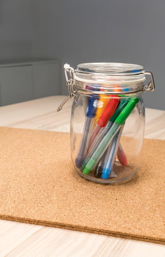 Le stylo de marqueur dans le support en verre clair d'arrondir-forme pour le bureau organisent photographie stock