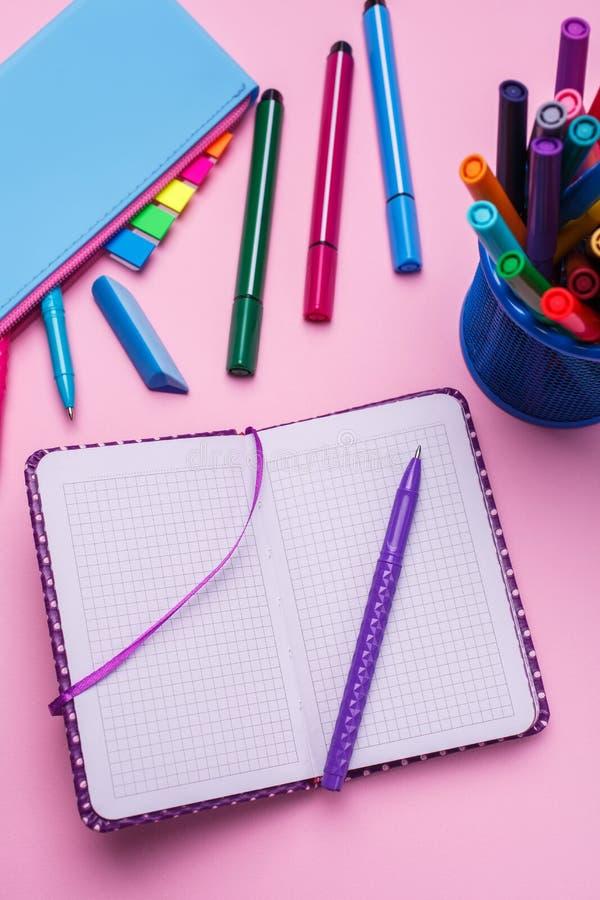 Le stylo est sur un carnet ouvert, à côté d'un cas de correction sur un fond rose images libres de droits