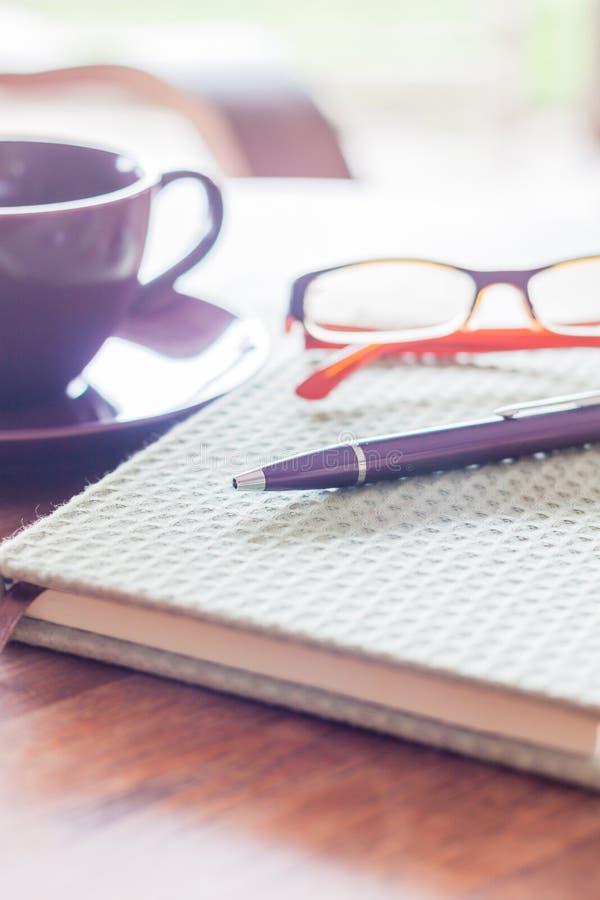 Le stylo et le vert ont couvert le carnet sur la table en bois image stock