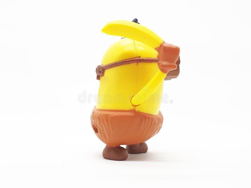 Le subordonné jaune de banane joue le modèle en plastique d'ignoble je film à l'arrière-plan d'isolement blanc photo libre de droits