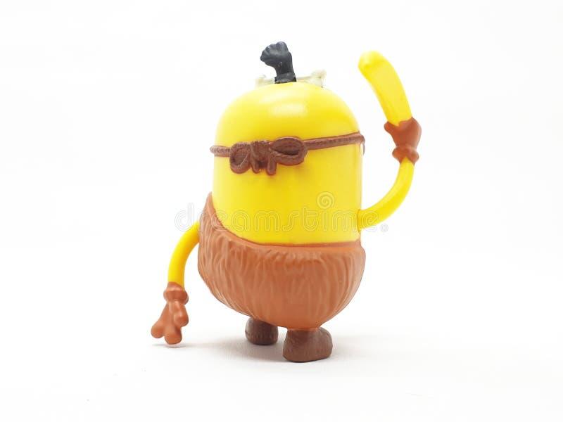 Le subordonné jaune de banane joue le modèle en plastique d'ignoble je film à l'arrière-plan d'isolement blanc image libre de droits
