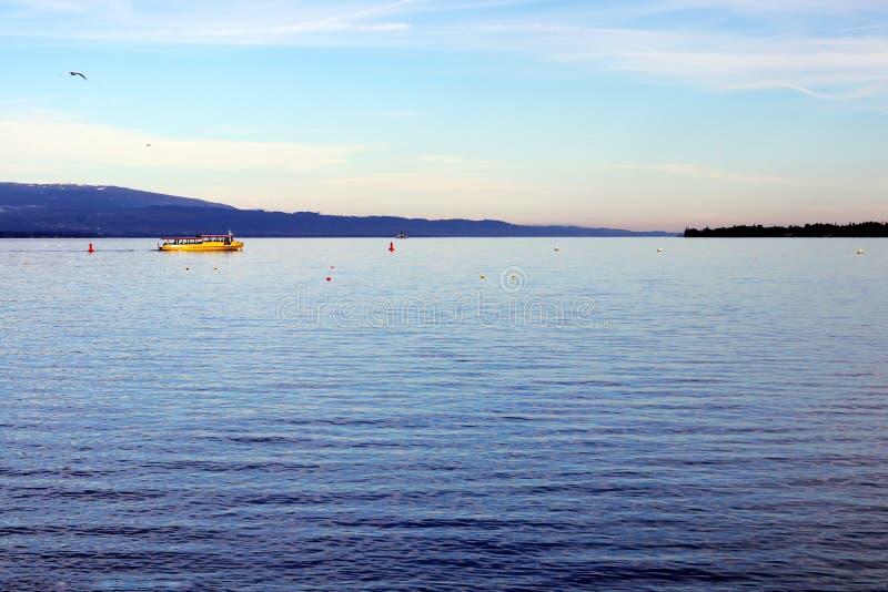 Le Suisse le Lac Léman avec le bateau jaune a appelé la mouette de mouette pendant le matin photos libres de droits