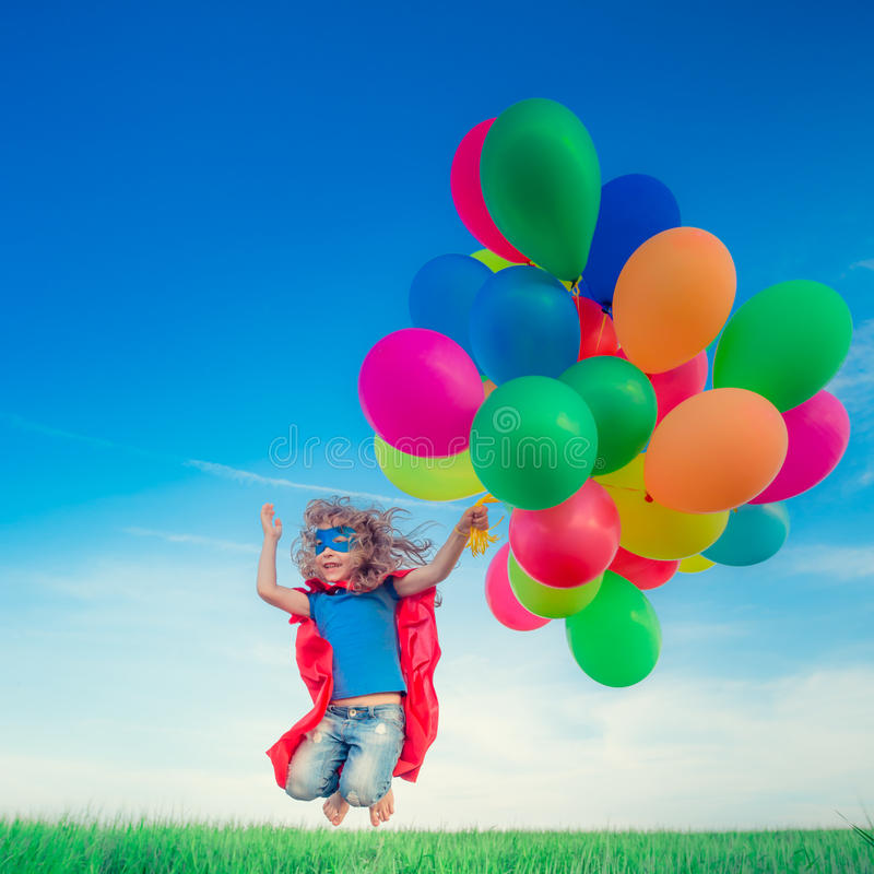 Le super héros avec le jouet monte en ballon au printemps le champ photo stock