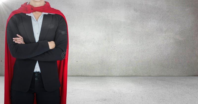 Le super héros de femme d'affaires avec des bras s'est plié contre le mur gris avec la fusée photo stock