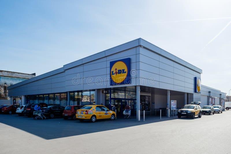 Le supermarché de Lidl avec des voitures a garé la lentille large de achat de personnes photos stock