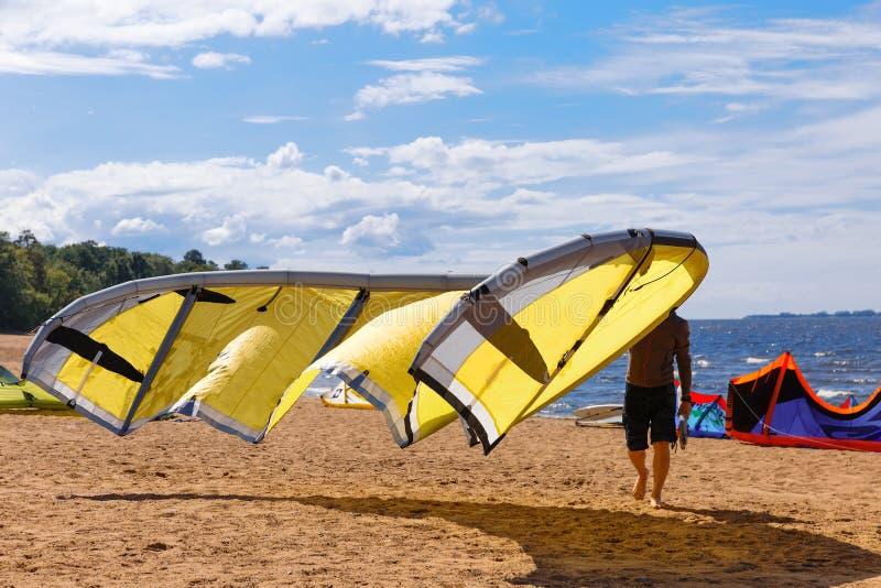 Le surfer de cerf-volant porte son cerf-volant jaune photographie stock