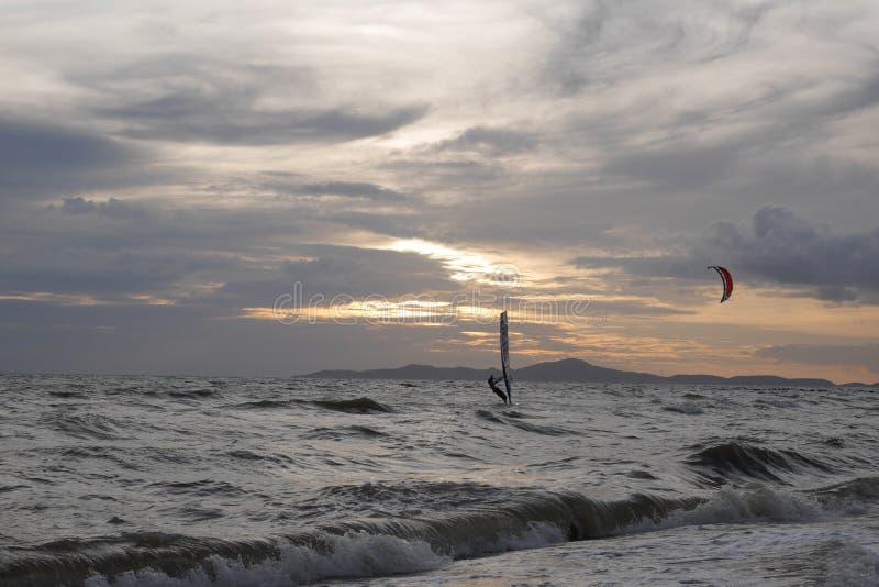 Le surfer de vent de début de soirée monte les vagues comme couchers du soleil images libres de droits