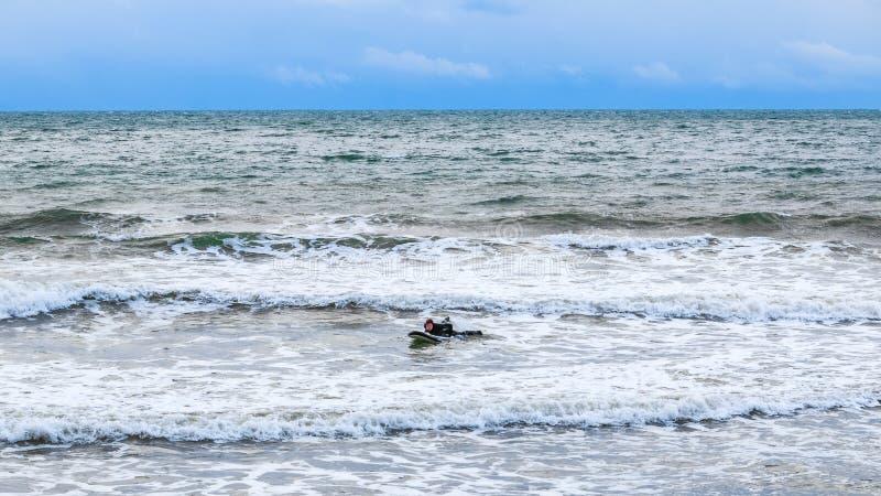 Le surfer essaye de monter sur les vagues intenses photos stock